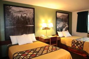A bed or beds in a room at Super 8 by Wyndham Queensbury Glens Falls