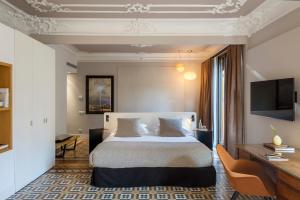 A bed or beds in a room at Alexandra Barcelona Hotel, Curio Collection by Hilton