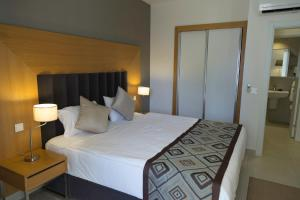 A bed or beds in a room at Ramada Hotel & Suites Kusadasi