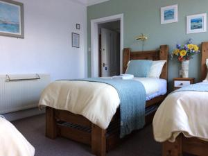 A bed or beds in a room at Cornerbrook Guest House