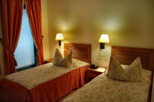 A bed or beds in a room at Albergo Hotel