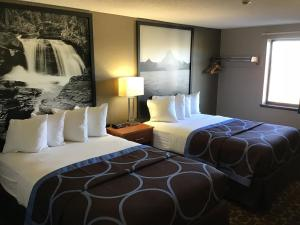 A bed or beds in a room at Super 8 by Wyndham Miles City