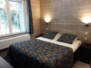 A bed or beds in a room at Logis l'Ermitage, Bistrot des Saveurs