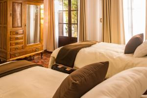 Cama o camas de una habitación en El Jardin De Su Merced B&B