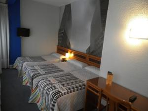 A bed or beds in a room at Hotel Photo Zabalburu