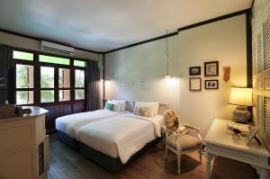 A bed or beds in a room at The Raweekanlaya Bangkok