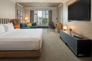 A bed or beds in a room at The Duniway Portland, A Hilton Hotel