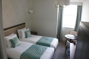 A bed or beds in a room at Legacy Hotel Victoria