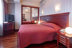 A bed or beds in a room at Hotel Epinal