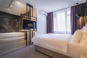 A bed or beds in a room at Level Luxury Suites