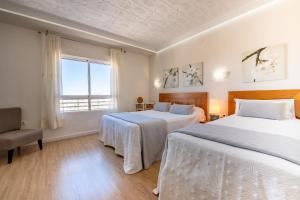 A bed or beds in a room at Alicante Skylights Apartments