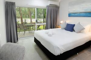 A bed or beds in a room at TiTree Village Holiday Apartments