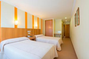 A bed or beds in a room at Hotel O Cruceiro