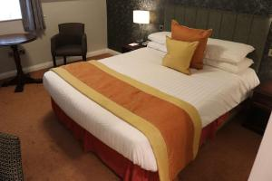A bed or beds in a room at The Villa Country House Hotel