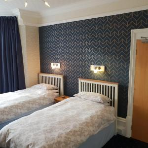 A bed or beds in a room at Abinger Guest House