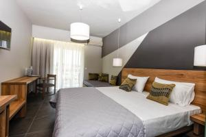 A bed or beds in a room at Exotica Hotel & Spa by Zante Plaza