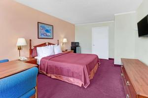A bed or beds in a room at Howard Johnson by Wyndham Tropical Palms Kissimmee