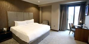 A bed or beds in a room at Ten Square Hotel