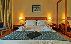 A bed or beds in a room at Ambassador Hotel Thessaloniki