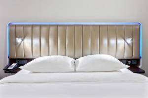 A bed or beds in a room at Park Inn by Radisson Kyiv Troyitska