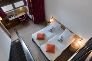 A bed or beds in a room at Hôtel l'Aigle des Neiges