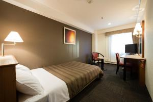 A bed or beds in a room at Ark Hotel Osaka Shinsaibashi