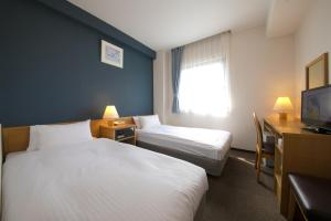 A bed or beds in a room at Heiwadai Hotel 5