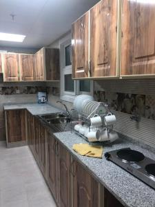 A kitchen or kitchenette at Al Rawda Apartments -Ajman