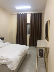 A bed or beds in a room at Al Rawda Apartments -Ajman
