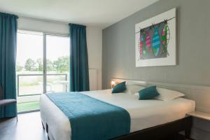 Un ou plusieurs lits dans un hébergement de l'établissement Hôtel du Golf Saint-Laurent,The Originals Relais