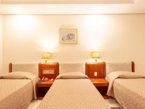 A bed or beds in a room at Real Castilha Hotel