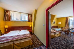 A bed or beds in a room at Hotel Kapitany Wellness