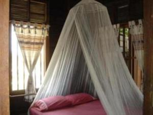 A bed or beds in a room at Ayothaya Riverside House