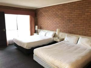 A bed or beds in a room at Essendon Motel