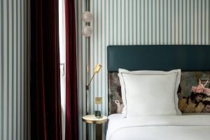 A bed or beds in a room at Hôtel du Rond-Point des Champs-Elysées - Esprit de France
