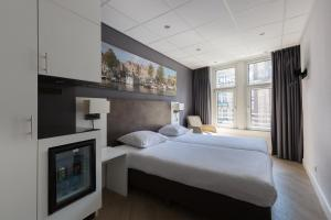 A bed or beds in a room at Hotel Amsterdam De Roode Leeuw