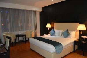 Кровать или кровати в номере The Olive Hotel, Juffair