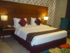 A bed or beds in a room at Al Manar Grand Hotel Apartment