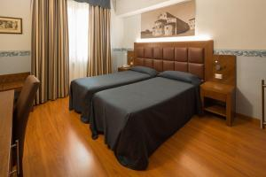 A bed or beds in a room at Hotel Terminus & Plaza