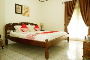 A bed or beds in a room at OYO 604 Cemara's Homestay