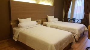 A bed or beds in a room at Muara Hotel and Mall Ternate