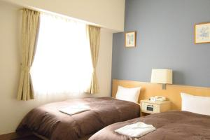 A bed or beds in a room at Hotel Raffinato Sapporo