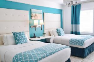 A bed or beds in a room at Beacon South Beach Hotel