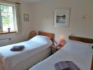 A bed or beds in a room at Bridge of Bennie Cottage