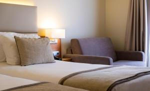A bed or beds in a room at Hotel Comfort Inn Ponta Delgada
