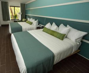 A bed or beds in a room at The Flagler Inn - Saint Augustine