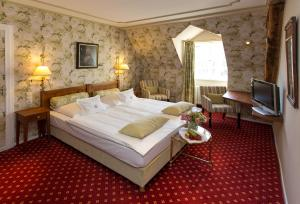 A bed or beds in a room at Romantik Parkhotel Wasserburg Anholt