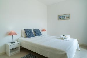 A bed or beds in a room at BmyGuest - Santa Luzia Beach Apartments