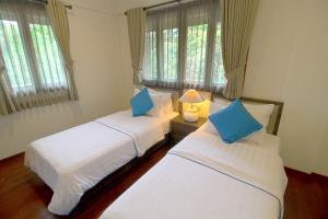 A bed or beds in a room at Banyu Biru Villa