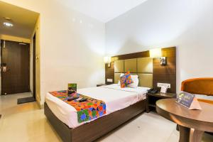 A bed or beds in a room at FabHotel The Pinnacle Kutchery Chowk